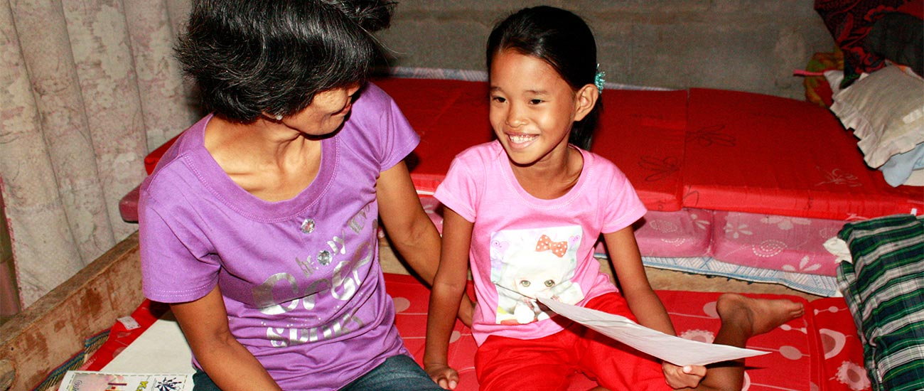 Young girl in the Philippines reads a letter from her sponsor