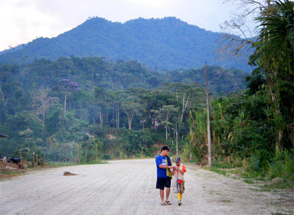Carlos speaks with a young kid as they walk down a road in Ecuador