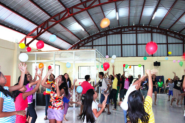 Teens play with balloons during a youth program activity