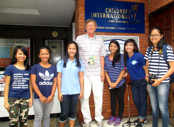 Chris Kent poses in front of a CI community center in the Philippines with six of his sponsored kids.