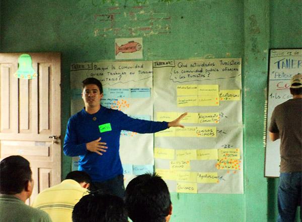 Carlos habla con una comunidad local sobre el desarrollar el turismo
