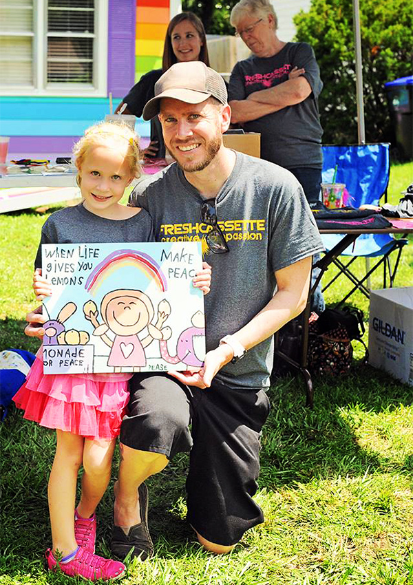 Jon and his daughter, Jayden, hold up a sign during their lemonade fundraiser in Topeka, Kansas.