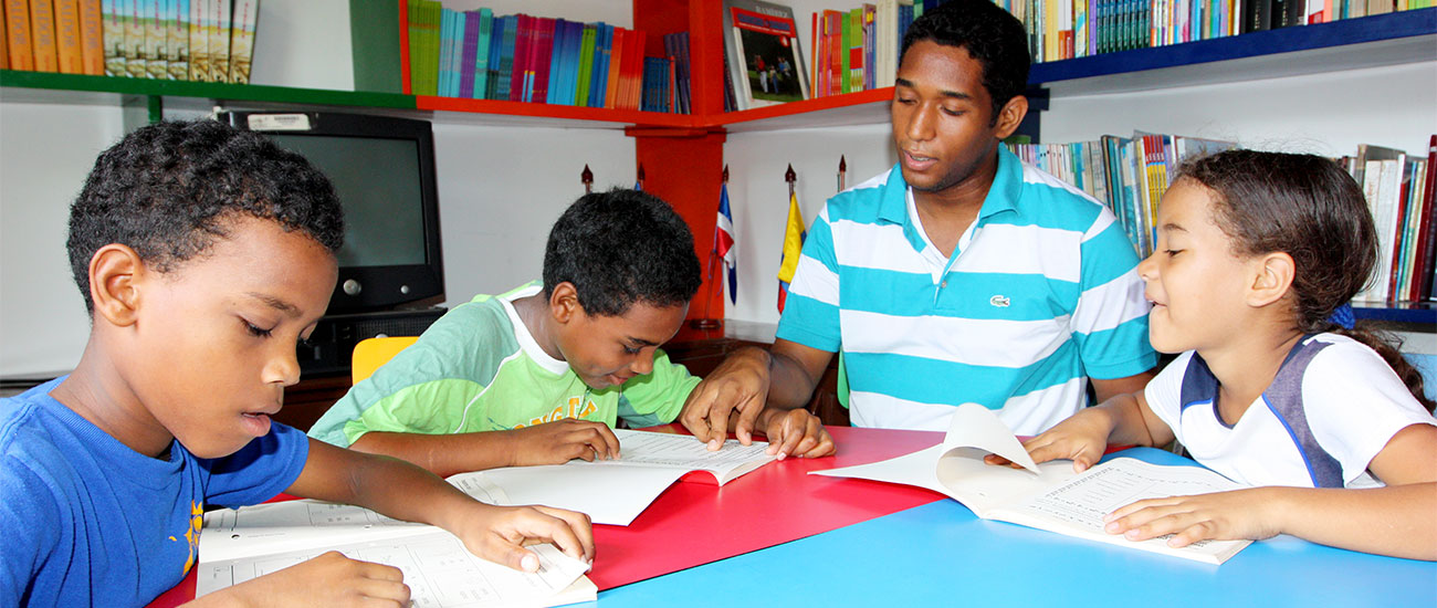 Older teen boy helps younger kids with homework at Colombia community center.