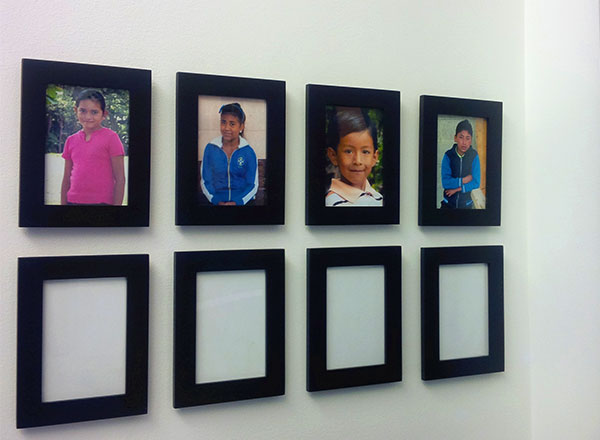 Photos of sponsored children hang in the Delos Advisors office
