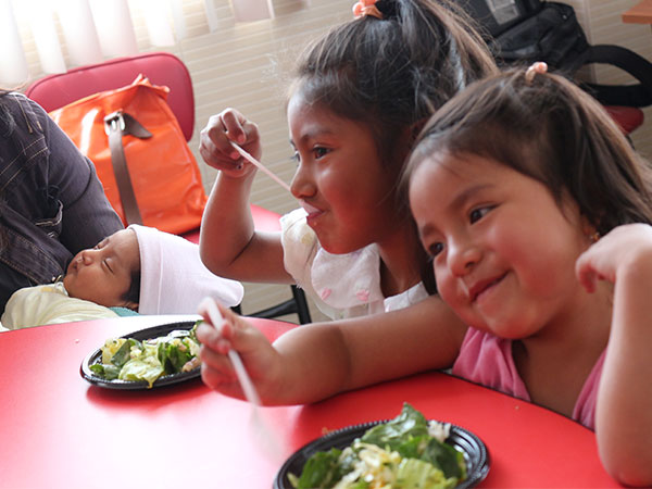 Two young girls from Ecuador sit side by side and try the salad, and they like it!