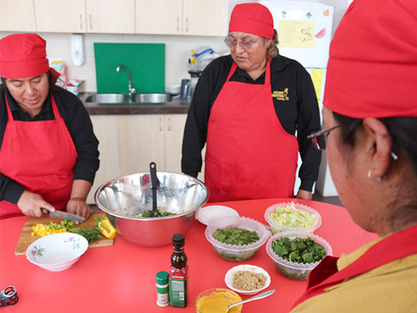 Ecuador moms prepare ingredients for making quinoa salad.