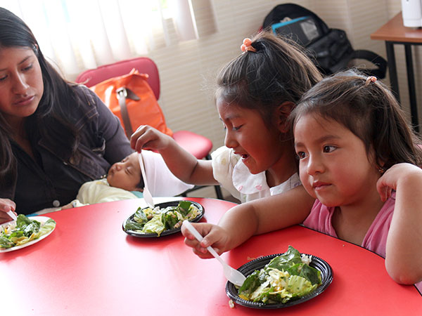 Two young girls from Ecuador sit side by side and try the salad.