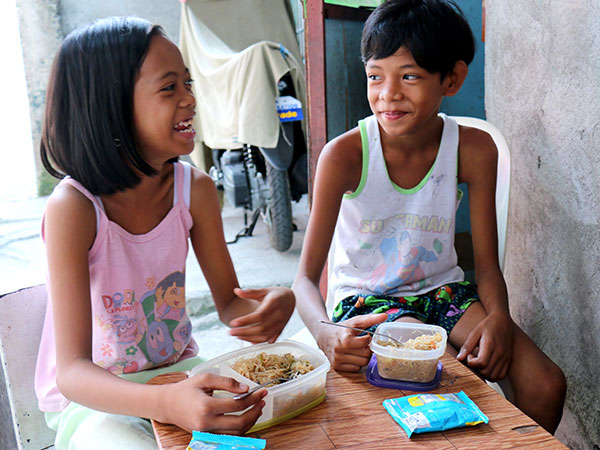 A boy and a girl eat noodles at a table.