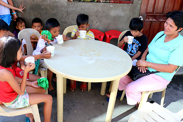 Children eat around a table outside with a volunteer mother.