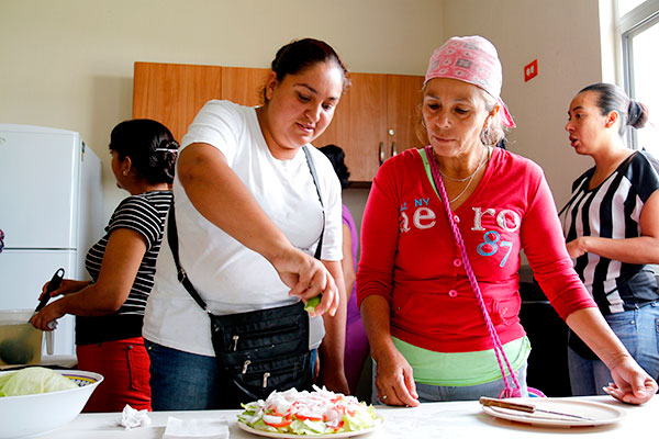 Two mothers prepare a salad and squeeze lime juice on top.