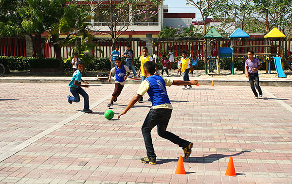 Kids participate in a Sports for Development game at the expansive community center outdoor court