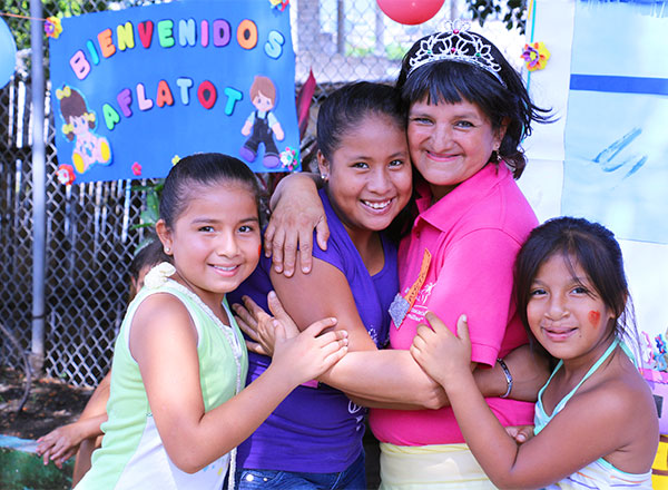 A volunteer hugs sponsored kids at an event in Guayaquil, Ecuador.