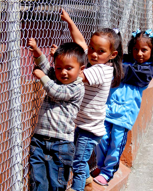 Three kids in Quito climb the fence at a community center
