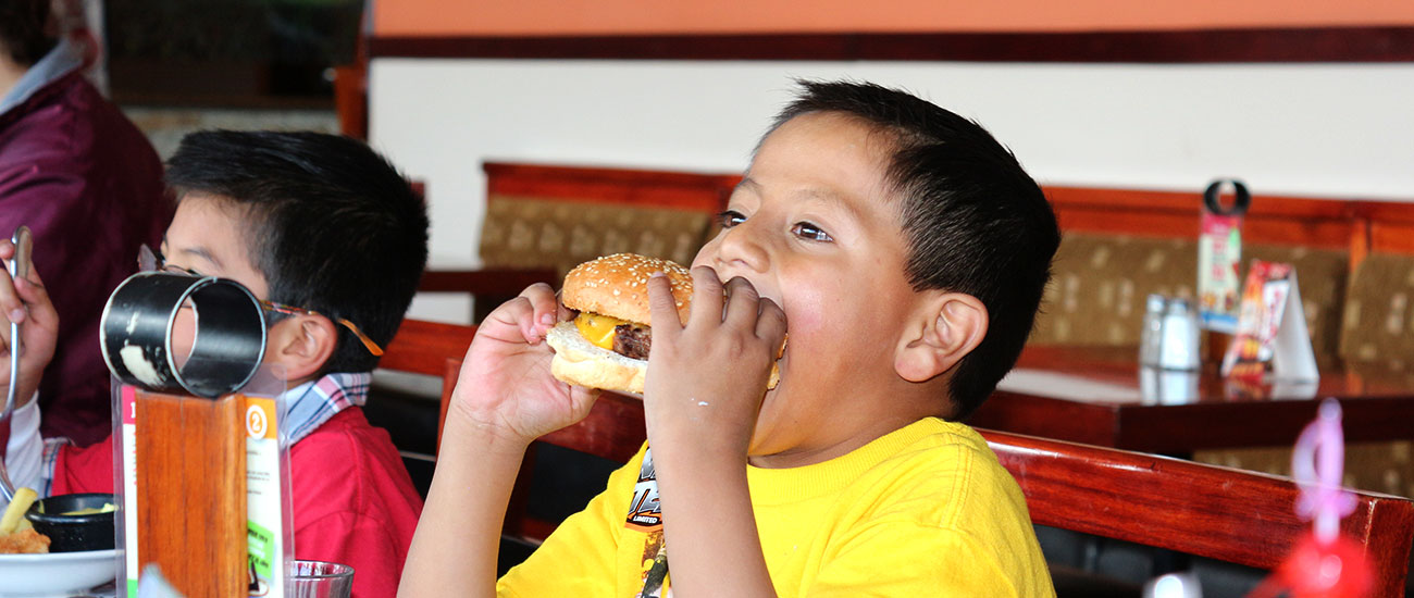 Boy takes a big bite of his hamburger.