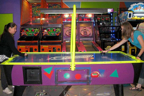 Bernardita and Shalynn play air hockey at an arcade