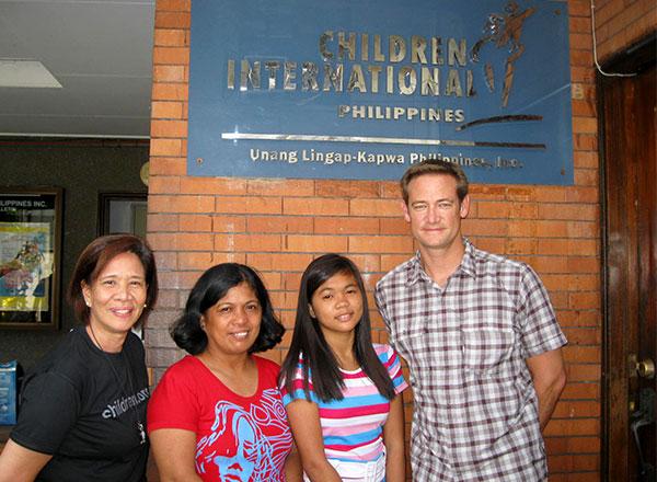 Kent se toma una foto afuera de un centro comunitario con su niña apadrinada, la madre de ella y la directora de la agencia de Children International en Quezon City.
