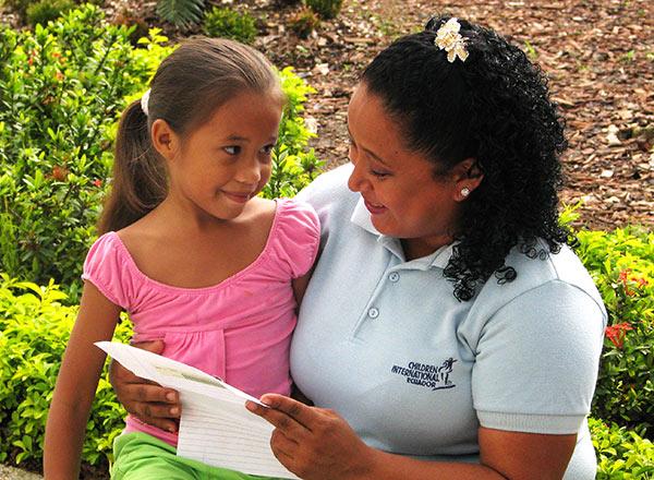 La voluntaria Pilar Ayala lea una carta a una niña en Guayaquil.