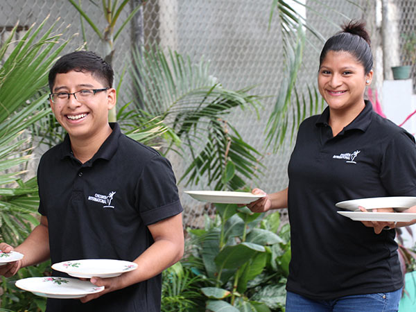 Youth practice carrying plates as part of their hospitality training.