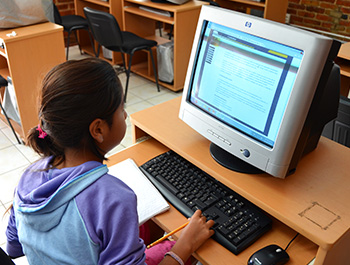 A girl uses Children International's computer lab to read an online article.