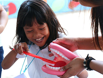 Children International teaches kids healthy behaviors, like the importance of brushing their teeth.