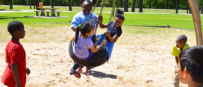 Children play on tire swing at a park in Arkansas.