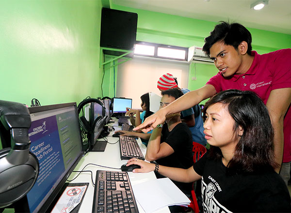 A group of teens uses the computer lab.