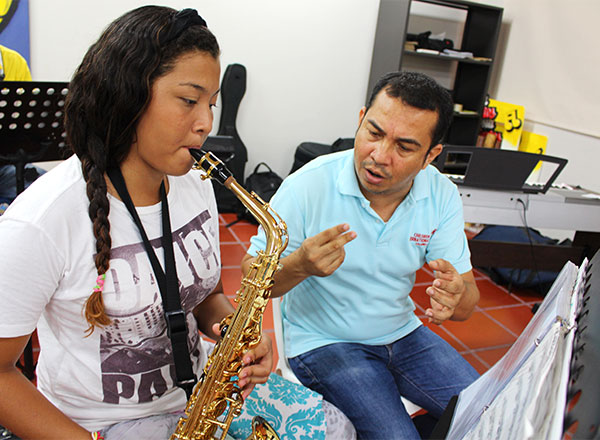 An instructor helps a student learn to play the saxophone