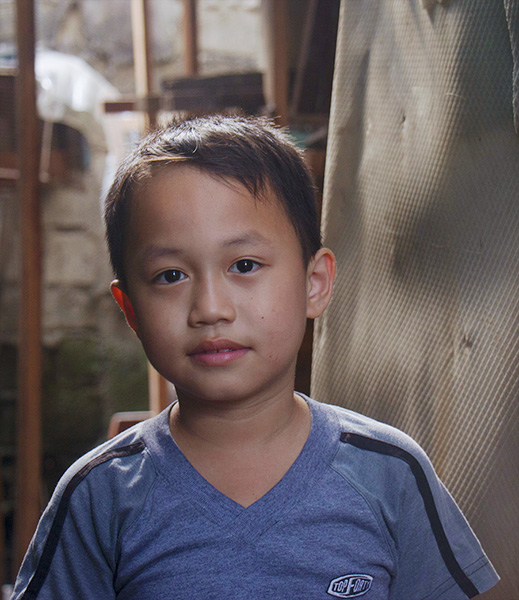 Portrait of 7-year-old Justine at his family's home in Manila, Philippines