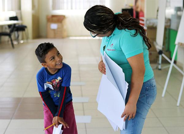 Un niño sonríe mientras habla con un instructor.