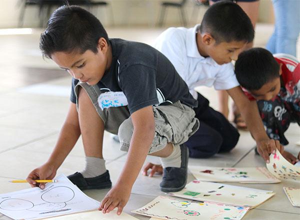 Un grupo de niños dibuja y escribe.
