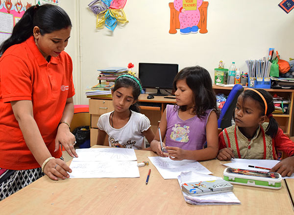 A Children International tutor helps three students with an assignment