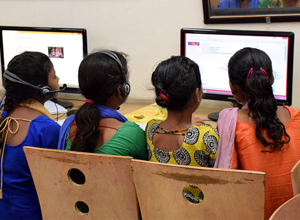 Four girls share a computer screen as they work together on an assignment