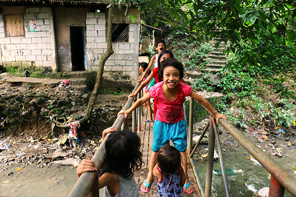 Kids in poverty play on a bridge over polluted water