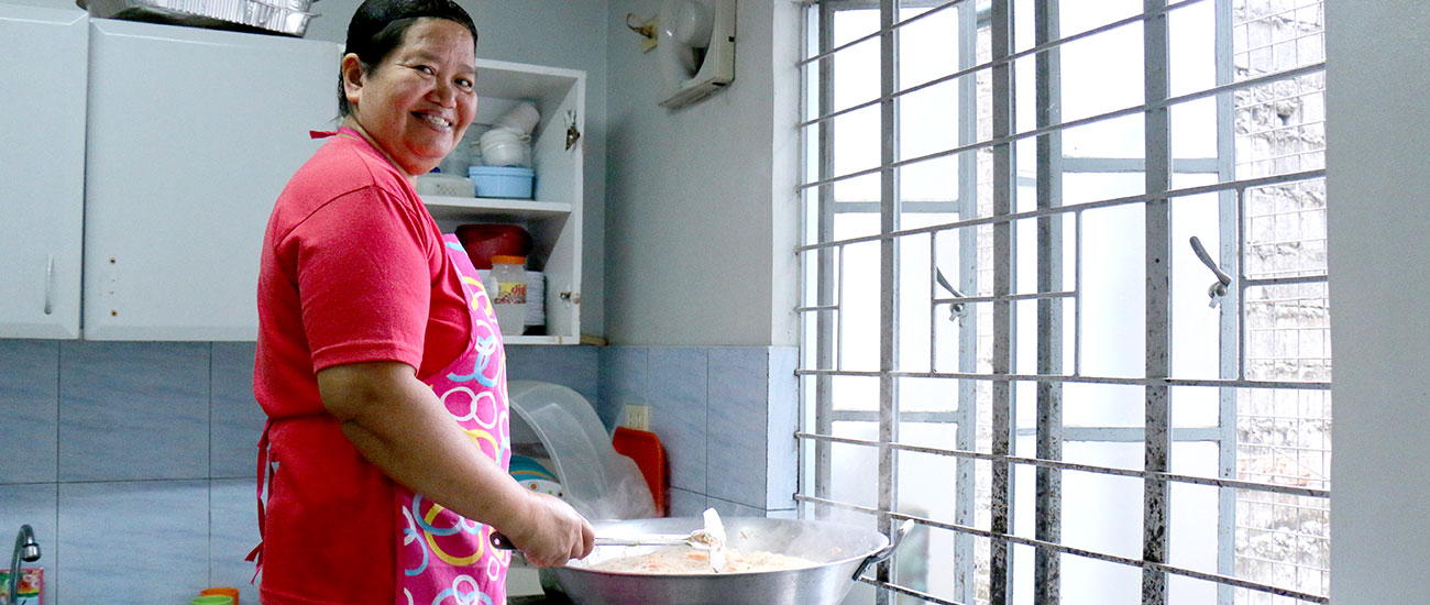 Volunteer mother stands in front of a giant pot filled with vegetables and noodles.