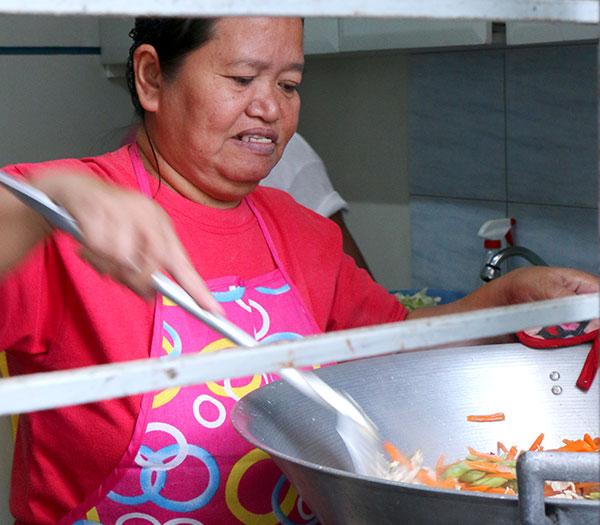 Madre voluntaria mueve una enorme olla de verduras con tallarines.