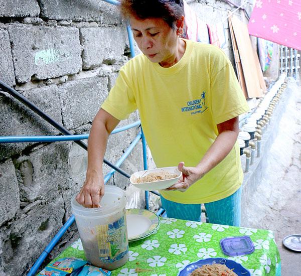 Madre voluntaria llena platos de tallarines.