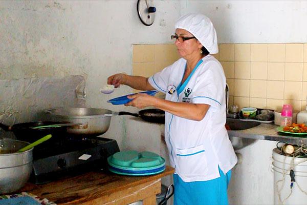 Carola llena de arroz blanco un plato.