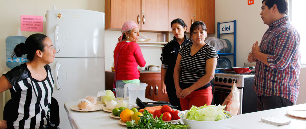Moms stand in a CI kitchen and listen to instructions about vegetables.
