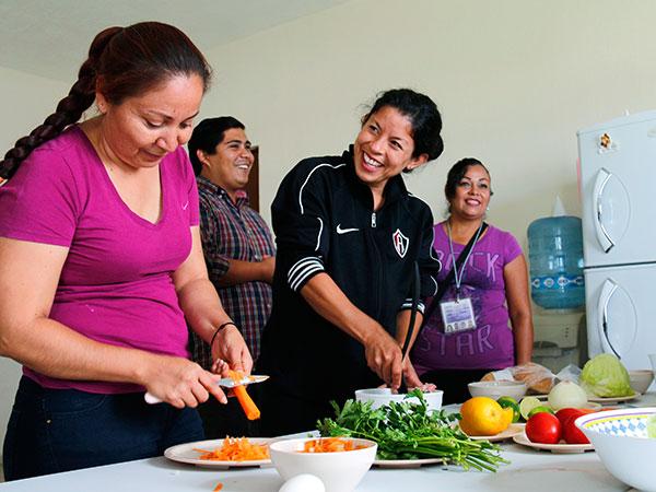 Mamás en México reciben instrucciones para preparar verduras.