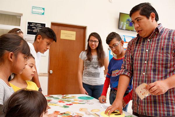 Un empleado de Children International les enseña a los niños sobre la diferencia entre las comidas saludables y las chatarras.