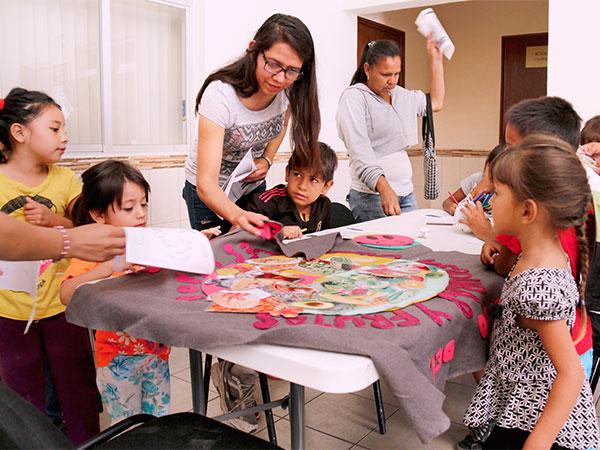 Niños categorizan recortes de comidas al colocarlos en un plato gigantesco.