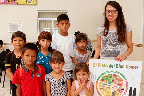 Niños con una voluntaria de Children International sosteniendo el rótulo El Plato del Bien Comer.