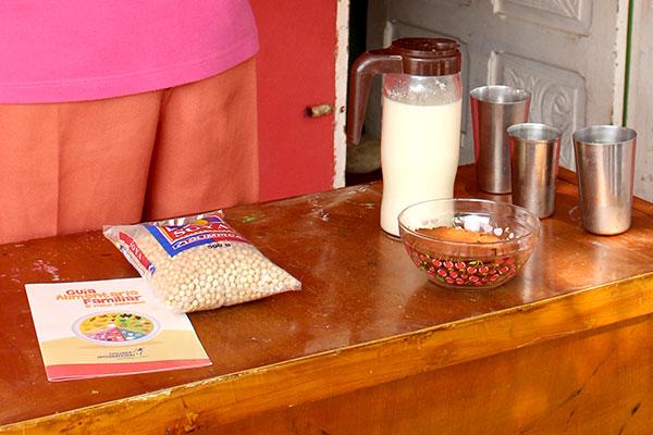 Primer plano de leche de soya en tazas de metal y una galleta de soya en un tazón.