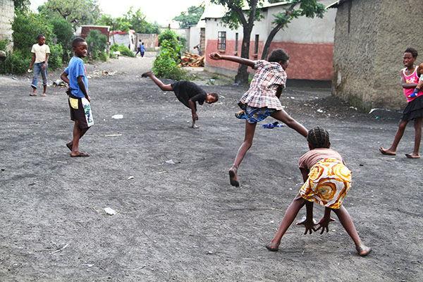 Poor children in Africa play ball in the dirty streets of their community