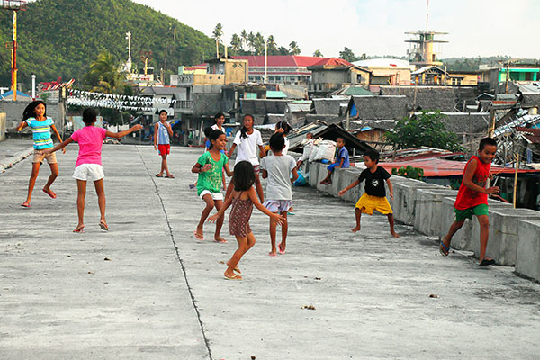 A group of kids play above a sewer in the Philippines