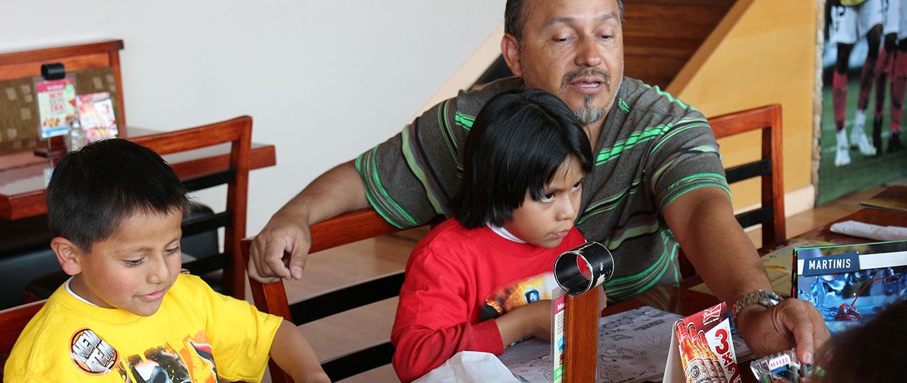 Man helps kids with menu decisions.