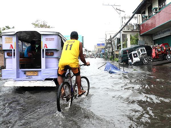 Los filipinos como este hombre en bicicleta son expertos para transportarse durante las inundaciones.