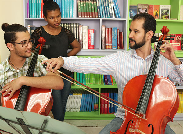 An instructor shows two students how to play the cello