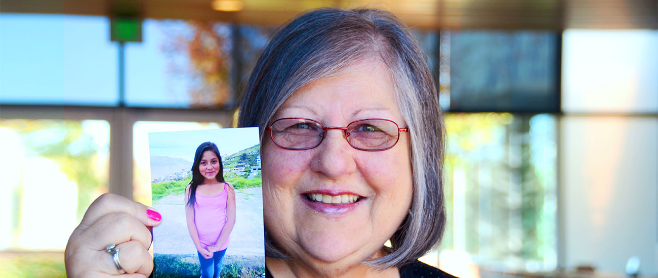 Sponsor and Team CI member Shirley Bowden holds up a picture of her sponsored child
