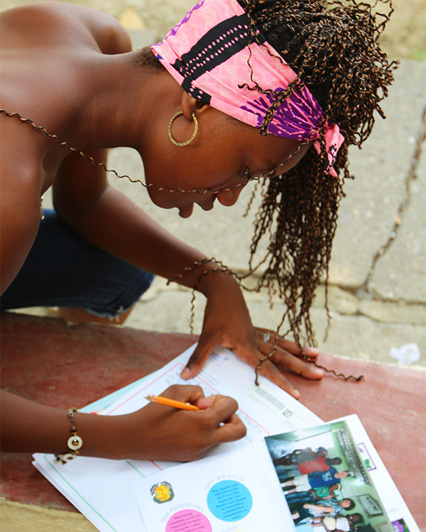 Dina keeps her sponsor's letter close as she writes her response.